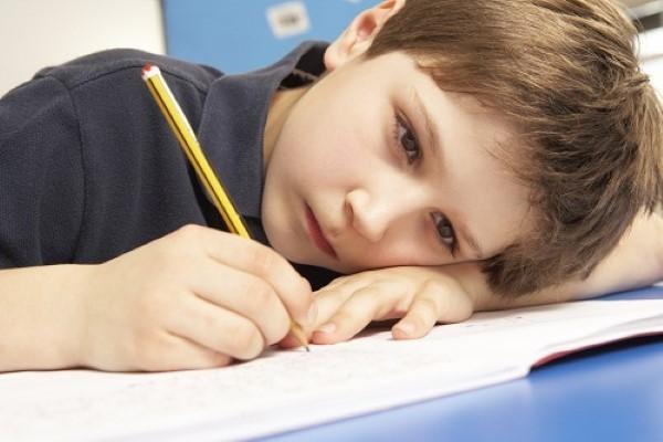 niño aburrido con deberes